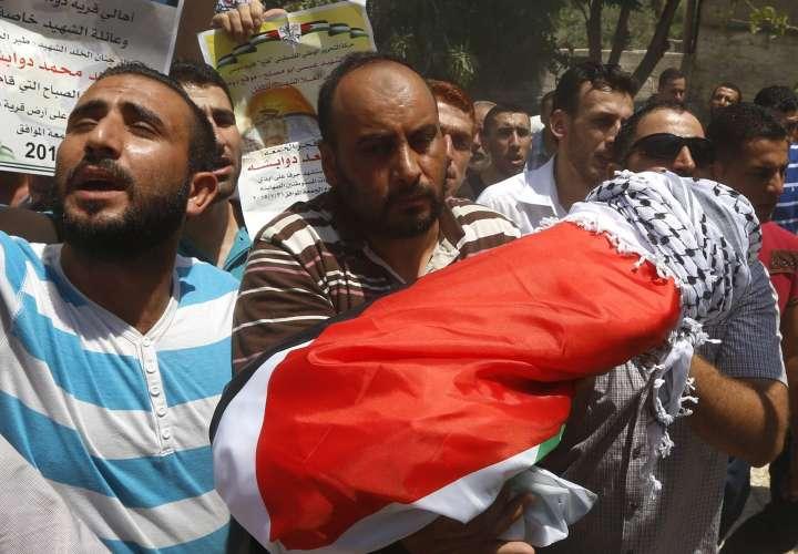 Un grupo de palestinos muestra el cuerpo sin vida de Ali Dawabsha, de 18 meses de vida, durante su funeral en Nablus (Cisjordania). EFE/Alaa Badarneh