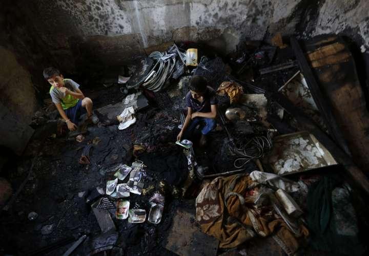 Un familiar observa una de las fotografías del bebé palestino de 18 meses Ali Dawabsha, que murió en un incendio provocado por colonos extremistas israelíes. EFE/Alaa Badarneh